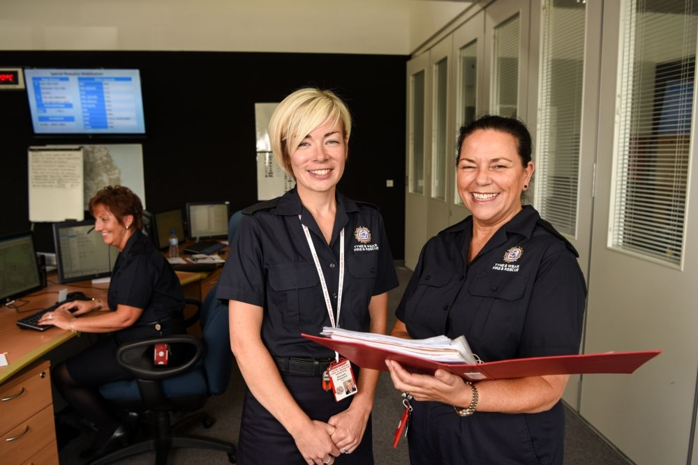 Two female public service workers smiling