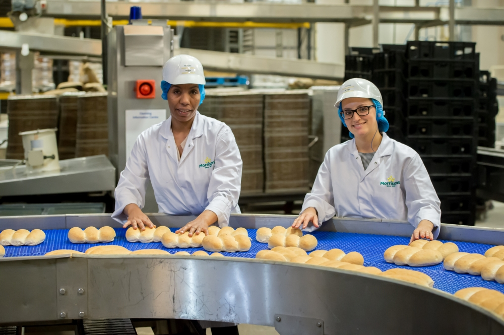 two women factory workers BAME at biscuit factory production line
