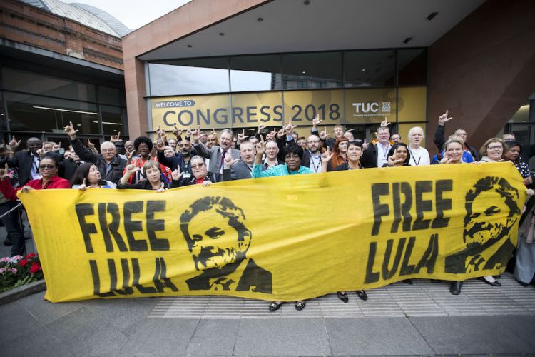 A group of delegates to the TUC Congress stand in front of a Free Lula banner