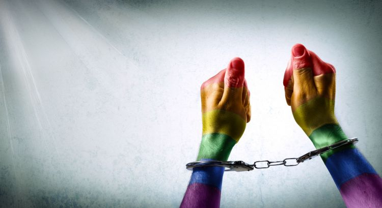 Handcuffed hands painted with gay pride flag