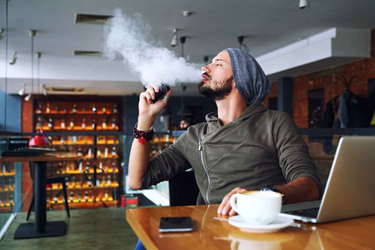 Young handsome hipster man with beard sitting in cafe with a cup of coffee, vaping and releases a cloud of vapor. Working at laptop and having a little break
