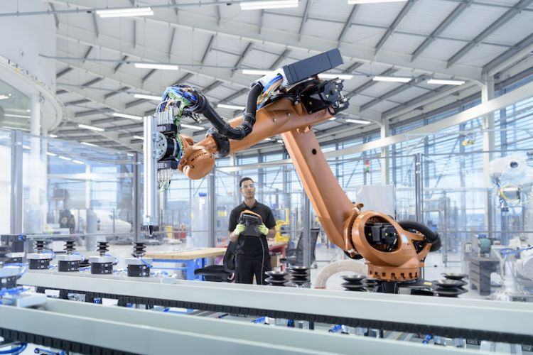 A factory worker holding a control pad manipulates a large robot