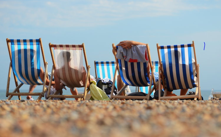 Four people relaxing on the beach on deckchairs