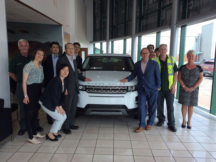 RENGO and TUC officials standing around a Range Rover on a workplace visit