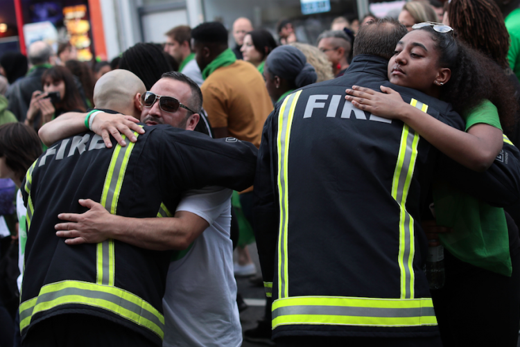 LONDON, ENGLAND - JUNE 14: People stop to hug firefighters during a silent march to St Mark's Park (Kensington Memorial Park)
