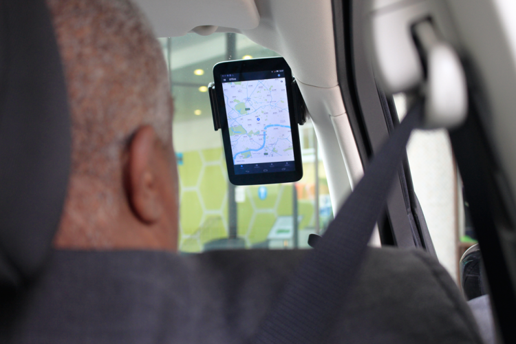 A driver looks at a mounted smartphone app screen