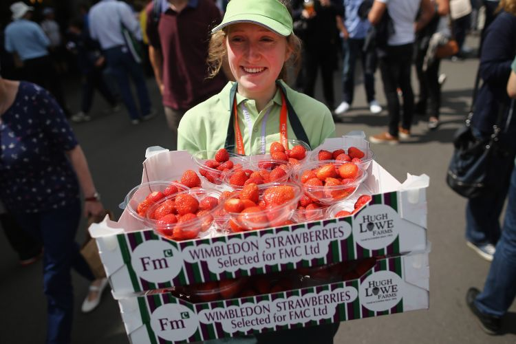 Photo of female worker at Wimbledon holding a basket of strawberries
