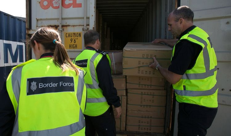 Border force workers unload boxes from the back of a lorry
