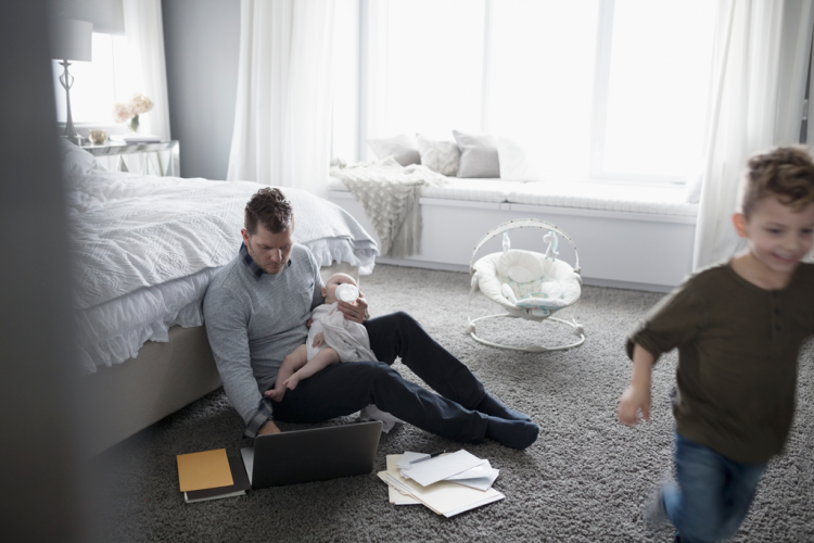 A man holding a baby attempts to work on a computer while another child runs across the bedroom