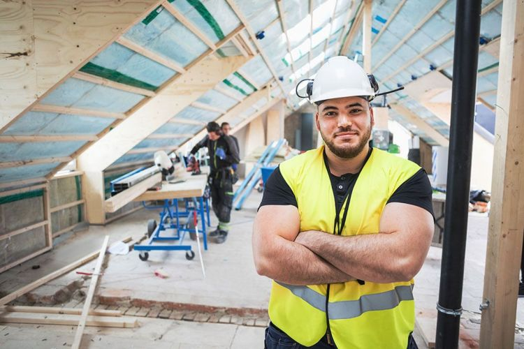 Portrait of confident manual worker standing with arms crossed at construction site