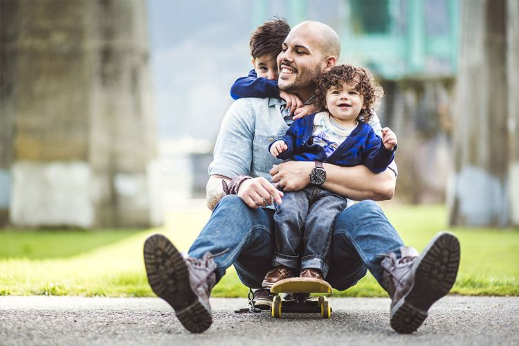A father sits on a skateboard while hugging a child and being hugged by another child behind him
