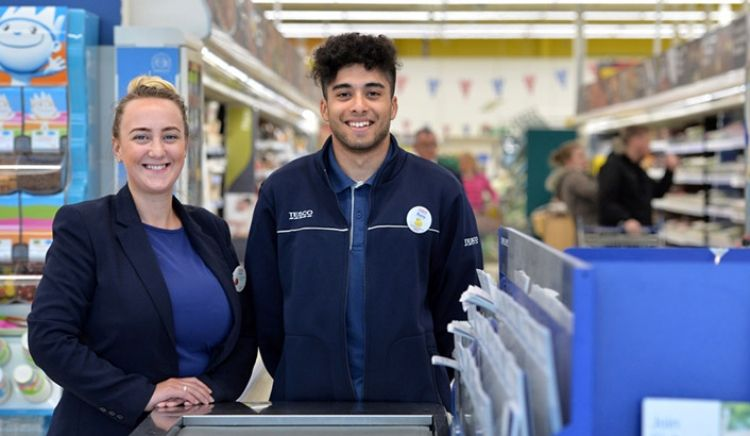 Two supermarket workers posing for the camera